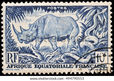 LUGA, RUSSIA - APRIL 12, 2016: A stamp printed by FRENCH EQUATORIAL AFRICA shows Black Rhinoceros and African Rock Phython, circa 1947.