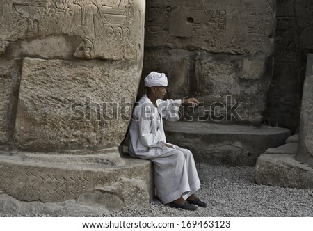LUXOR, EGYPT - JULY 19, 2010: Old Egyptian beggar sitting on a base column of Luxor temple. On July 19, 2010 Luxor, Egypt
