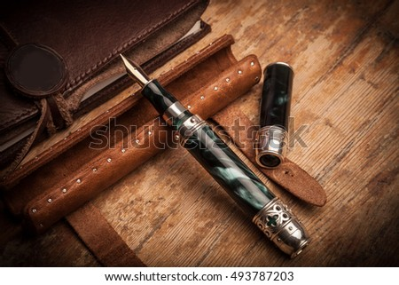 Luxurious fountain pen on a wooden background. Vintage pen