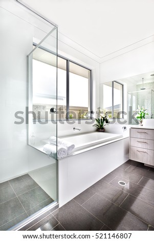 Luxury bathroom floor is made of shiny tiles. The bathing area is covered with glass panels that next to the white ceramic bath tub under the window. There are few towels against the mirror.