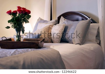Luxury bedding with roses on a tray. Lit only by the table lamp to create warmth.