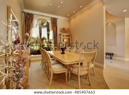 Luxury beige dining room interior with large arch window, golden curtains, vintage wooden table set for ten persons.And Decorative vase with dry branches. Northwest, USA