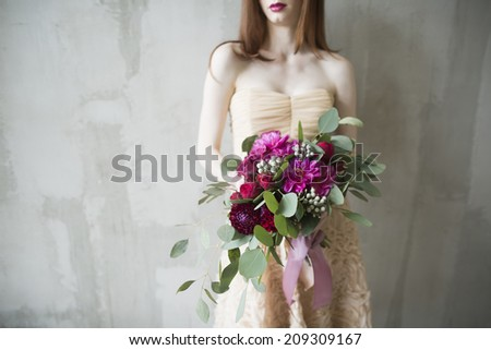 Luxury bride in a pink dress with a wedding bouquet in the wine color
