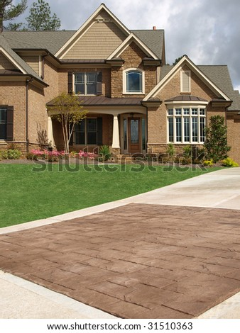 luxury model home exterior with stone driveway - Luxury Stone Exterior
