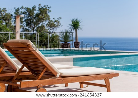 Luxury swimming pool and deck chair at the resort with beautiful sea view
