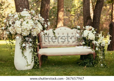 luxury wedding decorations with bench, candle and flowers composition on ceremony place