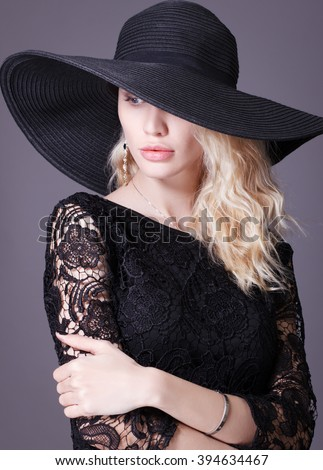 Luxury young woman in a big black hat .