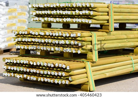 Lyckeby, Sweden - April 7, 2016: Stack of green pressure impregnated wooden poles with barcode price tags at the ends, at a public area behind a store.