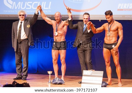 MAASTRICHT, THE NETHERLANDS - OCTOBER 25, 2015: Male bodybuilders Erik Stobbe celebrate their victory with officials on stage at the World Grandprix Bodybuilding and Fitness of the WBBF-WFF