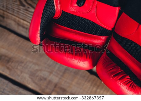 Macro detail of red boxing gloves. Wooden background.