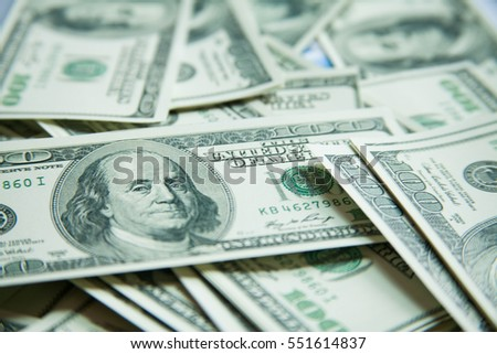 Macro shot of Benjamin Franklin's portrait on a 100 US$ money note, with defocused background of many more identical money notes in a mess.