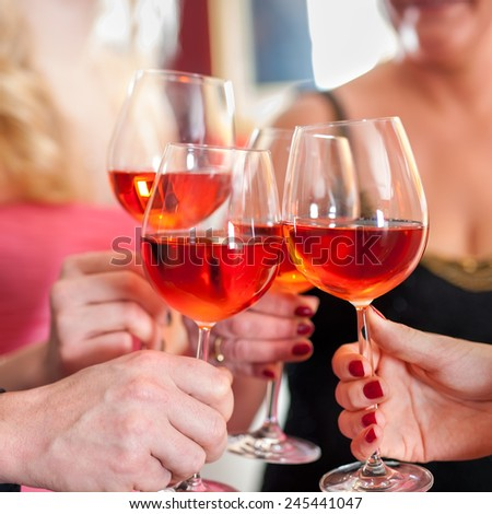 Macro Shot of Hands Raising Glasses of Tasty Red Wine in a Social Gathering.