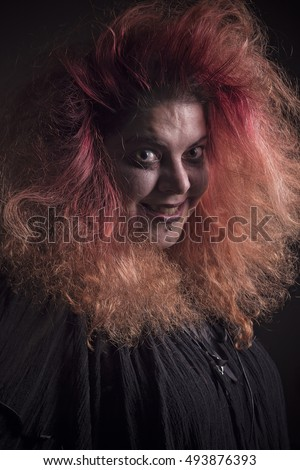 Mad horror girl with red hair in the dark, insane and scary looking