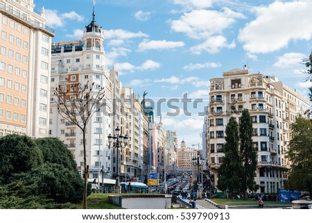 Madrid, Spain - November 13, 2016: Gran Via in Madrid. It is an ornate and upscale shopping street located in central Madrid. It is known as the Spanish Broadway. Sunny day