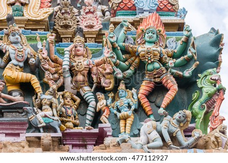 Madurai, India - October 19, 2013: Closeup of two images representing the fierce goddess Kali. In one she defeats the Man. Facade of South Gopuram at Meenakshi Temple.