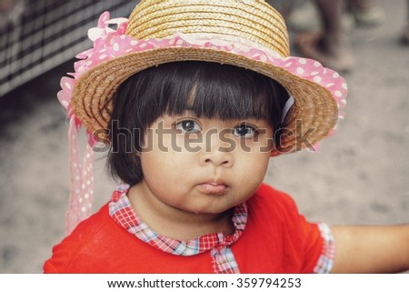 Mae Hong Son,Thailand - August 16, 2015 : Little cute Thai girl wearing hat made of palm leaves, she was with her mother during shopping in a local market in Mae Hong Son,Thailand