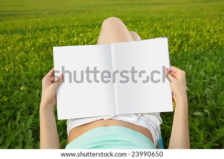 Magazine of in a lap reading person against a field