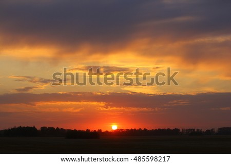 Magical sunset with dramatic sky, misty field and forest.