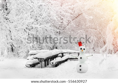 Magical winter forest and smiling snowman during a snowfall. Camping. Picturesque nature.