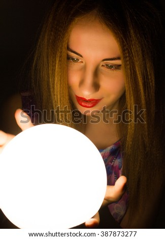 Magnificent Redhead fortune teller holding crystal ball. beautiful woman tries to look into the future