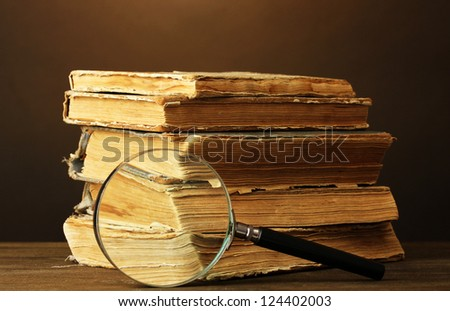 Magnifying glass and books on brown background