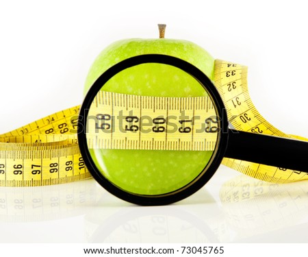 Magnifying glass and green apple wrapped with the meter, on a white background.