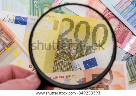 magnifying glass on different euro bills