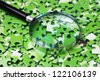 magnifying glass on pile of green puzzle - stock photo
