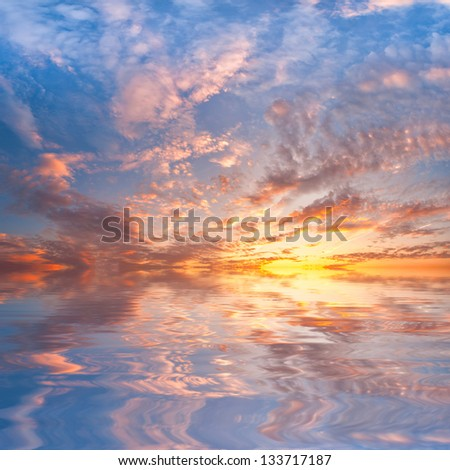 Majestic sunset over sea with reflection in water, beautiful clouds in the sky