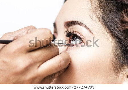 Makeup artist applying mascara on a lady inside a beauty parlor. Close up.
