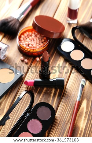 Makeup brush and cosmetics on brown wooden table
