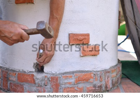 Making a hole in a concrete by hands with hammer and chisel