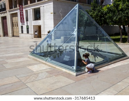 MALAGA, SPAIN - SEPT 10: Three years old girl observing roman ruins through the glass pyramid of Alcazaba St. September 10, 2015 in Malaga, Andalusia, Spain