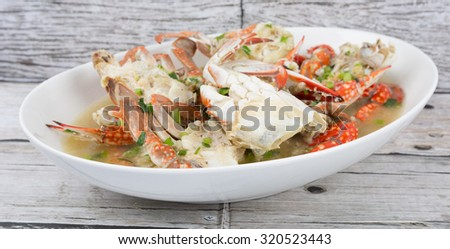 Malaysian dish clear crab soup in an oblong plate over wooden background