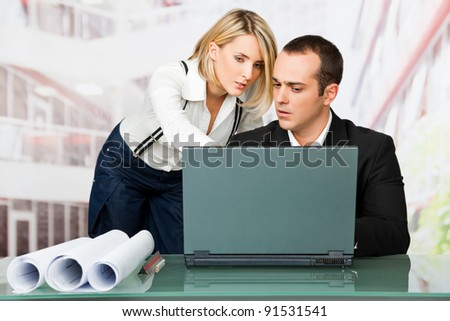 Male and female architects discussing behind laptop and blueprints