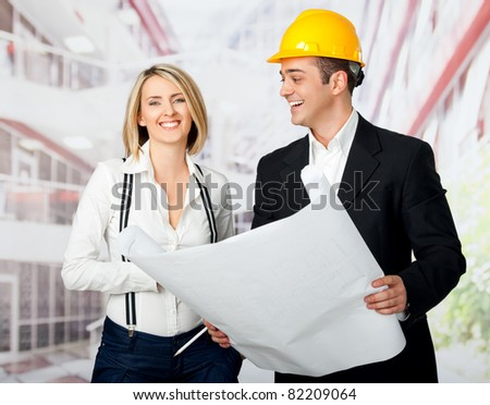 Male and female architects holding blueprint and smiling, man wearing yellow hardhat