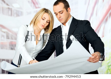 male and female architects looking at blueprint