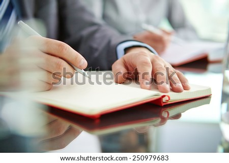Male and female hands writing in notebooks