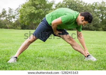 Male athlete stretching legs at a park