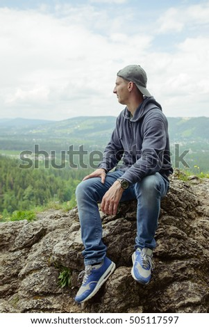 Male backpacker resting and enjoying the mountain sitting on rock in sun light.
