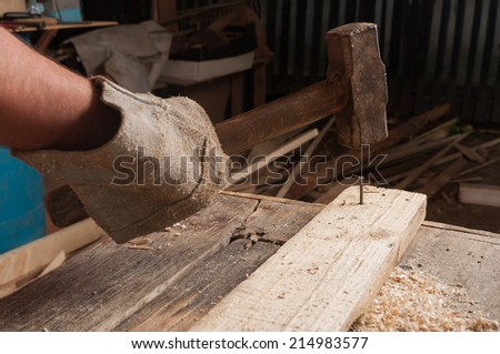 Male carpenter using a big hammer hitting a nail on wood in his workshop