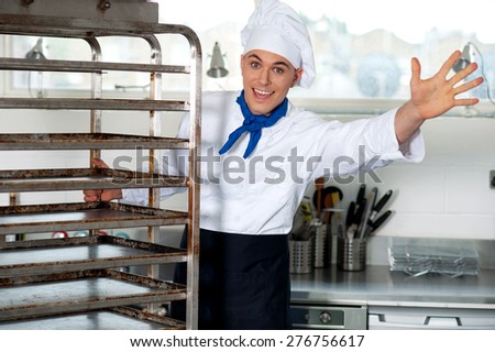 Male chef in kitchen holding food tray rack