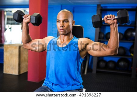 Male determined athlete exercising with dumbbells in fitness studio