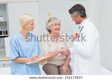 Male doctor and senior patient shaking hands while nurse writing reports in clinic
