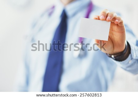 Male doctor holding empty white card