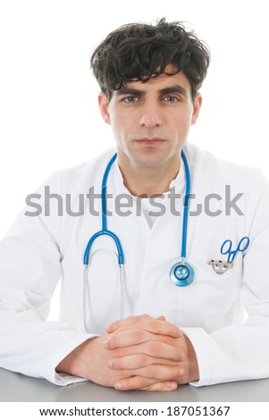 Male doctor sitting at desk isolated over white background