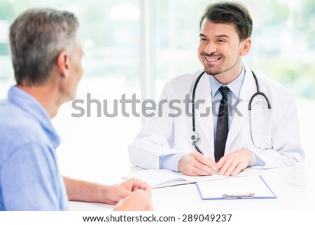 Male doctor talking with patient and writing down recipe for medicine.