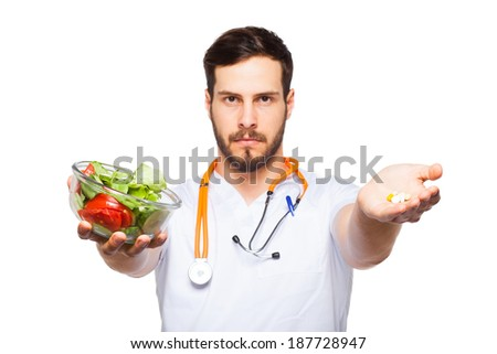 male doctor with stethoscope showing salad in one hand and pills on the other