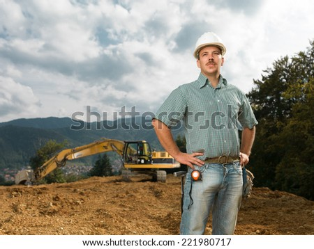 male engineer standing on construction site with excavator in background