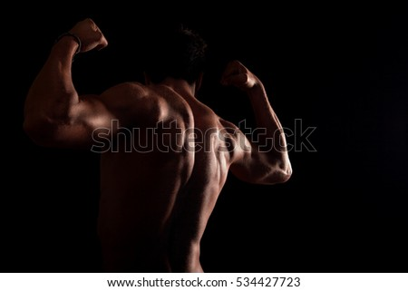 Male fitness model, bodybuilder back pose on black background